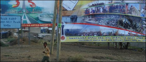 "Boy walks past campaign billboard for the EPRDF next to TPLF 35th anniversary billboard. EPRDF billboard says, ""electing EPRDF means ensuring the continuation of development and the renaissance of the country."" TPLF billboard says, ""we will repeat our past victories."""