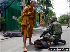 A monk watches a soldier detain a protester in Bangkok on 19 May 2010