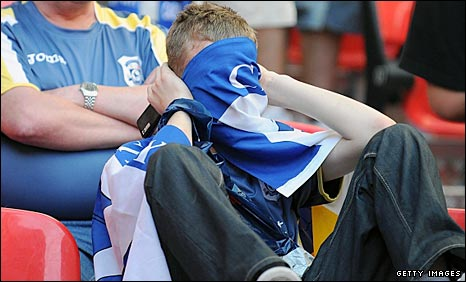 A Cardiff City fan hides his face in despair after the Bluebirds' 3-2 defeat by Blackpool in the Championship play-off final