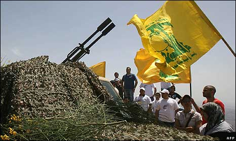 Lebanese tourists look at a Hezbollah's anti-aircraft machine-gun displayed in the area of Sujud in southern Lebanon on 22 May 22, 2010