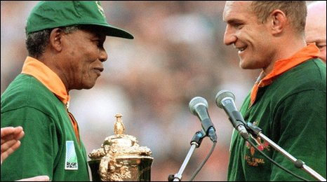 Nelson Mandela congratulates South African captain Francois Pienaar before handing him the Rugby World Cup trophy at Ellis Park in Johannesburg, 24 June 1995