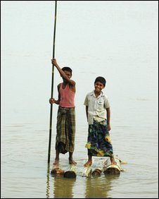 Two boys on a makeshift bamboo raft