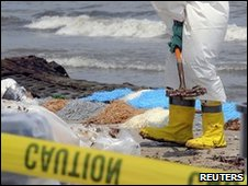 A BP contract worker cleans the beach at Port Fourchon, Louisiana