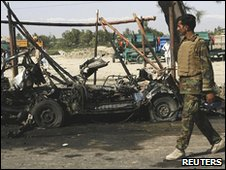 Afghan security officer walks past the wreckage of a bombed car
