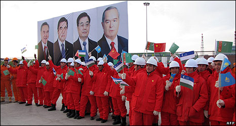 Workers hold flags at opening of gas pipeline to China in Samandepe, Turkmenistan, 14 Dec 09