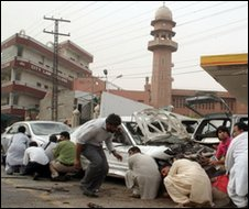 Pakistani media take cover outside a mosque in Lahore, 28 May