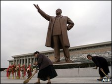 Women sweep the steps in front of the Kim Il-sung statue