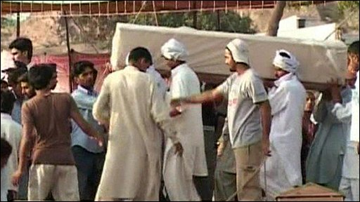 Men carrying coffin to grave in Lahore