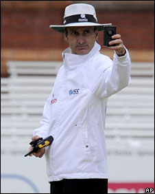 Umpire Billy Bowden checks his light meter