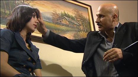 Dr Abbas al-Sihn (l) examines a prospective patient