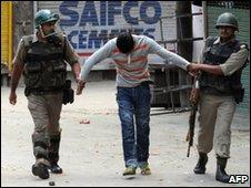 Indian paramilitary soldiers detain a Kashmiri youth in Srinagar