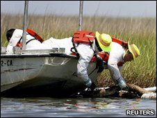 BP contract workers rotate an absorbent boom to clean up the marsh west of Lake Felicity near Cocodrie, Louisiana
