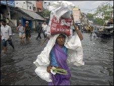 A woman walks through a flooded street after heavy rains in the southern Indian city of Vishakhapatnam on May 20, 2010