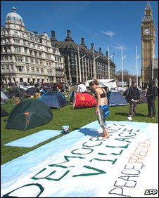 "A woman paints a banner in the ""Democracy Village"" in Parliament Square"