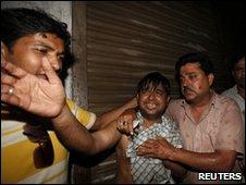 Men grieve near the scene of the fire in Dhaka, 3 June