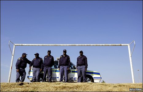 South African policemen stand underneath a goal as they watch people stand in line to view a replica of the World Cup trophy at a community center in Soweto, Johannesburg