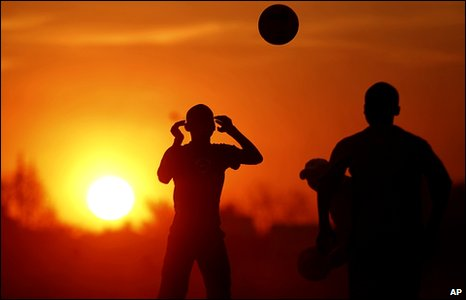 South African kids playing football as the sun sets in Soweto, South Africa