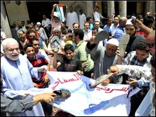Egyptians worshippers symbolically hit an Israeli flag with their shoes
