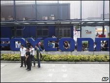 Staff gather at the company sign outside Foxconn&#039;s plant in Shenzhen on 26 May 2010