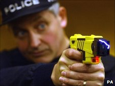 Policeman demonstrates using a Taser stun gun
