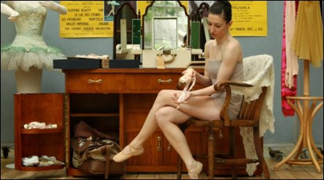 "Royal Ballet Principal Mara Galeazzi looks at a ballet shoe, part of a recreation of Margot Fonteyn""s dressing room, which will form part of Invitation to the Ballet: Ninette de Valois and the Story of the Royal Ballet"