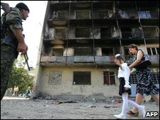Woman and child walk past burnt-out building in Tashkinvali , 2008