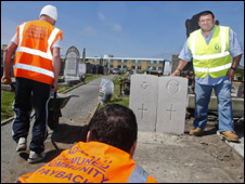 Community payback supervisor Sid Giles [R] near the grave