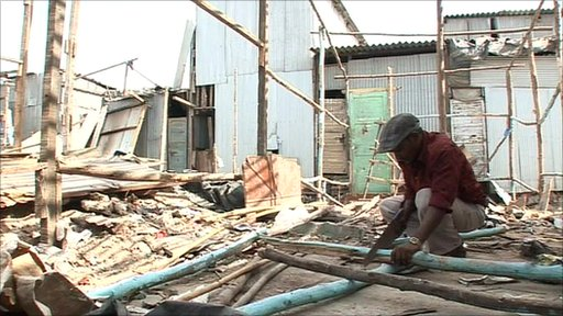 A man rebuilds his home following a demolition.