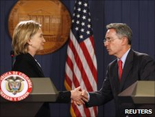 Hillary Clinton (left) and Alvaro Uribe shake hands at a news  conference on 8 June 