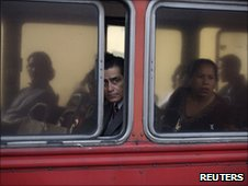 Passengers in a bus look at one of the crime scenes