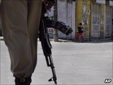 A paramilitary soldier patrols a deserted street in Srinagar on Sunday, June 13, 2010