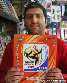 Newsagent Ronaldo Faria holds one of the Fifa World Cup albums
