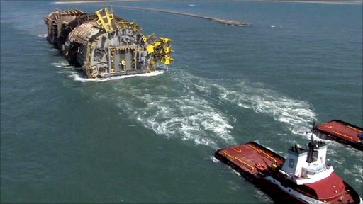 A gigantic oil platform is towed out to sea.