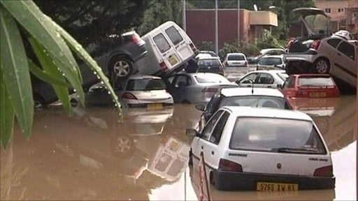Cars piled high in flood water