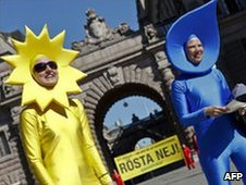 Greenpeace activists dressed up as water and sun elements demonstrate outside the Swedish parliament building