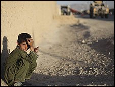 An Afghan boy sits at the edge of a cordon set up by US Army MP's of the 293rd Battalion during an operation by a US Army Explosive Ordnance Disposal (EOD) team to recover a weapons cache in Kandahar City