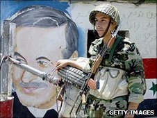 Syrian soldier next to post of Hafez al-Assad