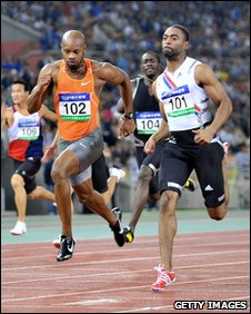 Asafa Powell (left) races Tyson Gay