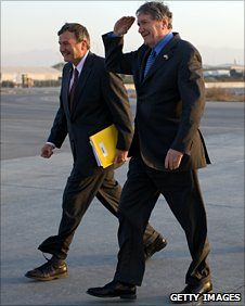 Richard Holbrooke (R) salutes while walking next to Karl Eikenberry (L) on their way to greet Gen Stanley McChrystal after arriving on 18 November 2009 in Kabul