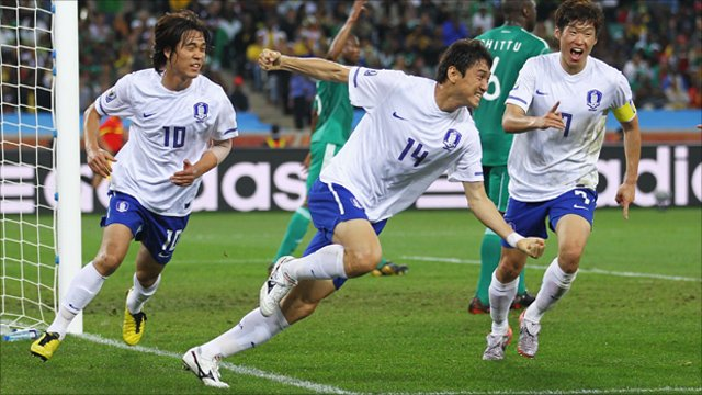 Lee Jung-Soo of South Korea celebrates with team mates after scoring the equalising goal