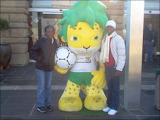 Two reporters with a lifesize World Cup mascot