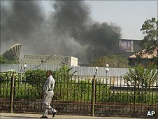 A man walks past the southern headquaters of Yemen's intelligence services building in Aden as black smoke billows from it following an attack on 19 June 2010