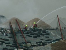 Firefighters on rubbish pile