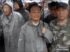 Chinese Premier Wen Jiabao stands under the rain during a visit to the flooded town of Luozhen in Fuzhou