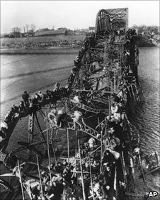 Korean refugees attempt to cross a wrecked bridge over the Taedong River