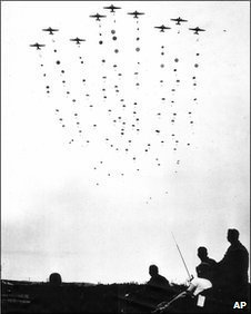 Image of a dozen planes high in the sky with hundreds of parachuters jumping