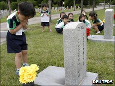 A child pays tribute to a fallen soldier at the National Cemetery in Seoul on 22 June 2010