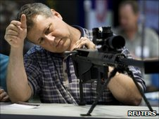 Man looks at big gun at National Rifle Association meeting