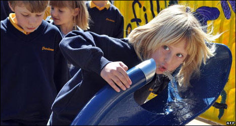 Girl drinks water from fountain