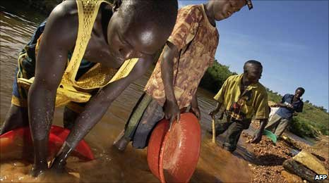 Congolese miners digging for gold on banks of the Iga river